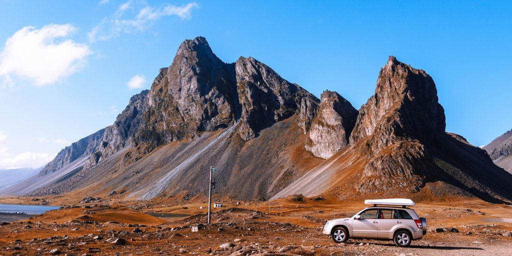 gray-SUV-parked-near-rock-cliffs