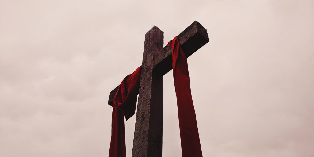 low-angle-view-of-cross-with-red-garment