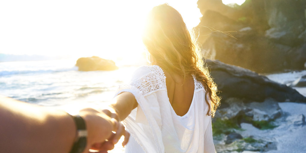 person-holding-woman's-hand-beside-sea-while-facing-sunlight